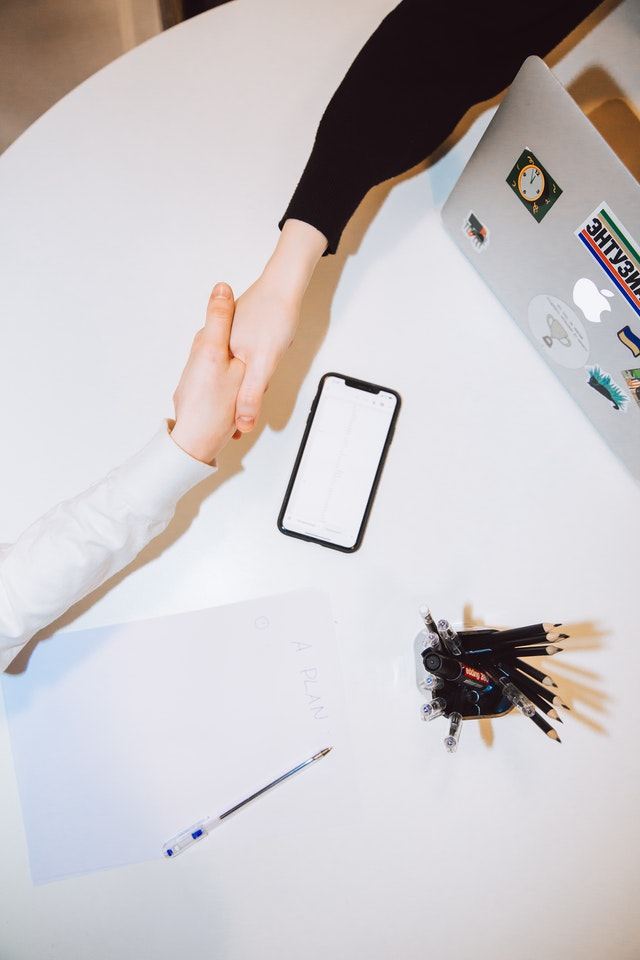 Shaking hands across a white desk with a phone and paper on it.